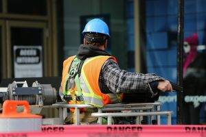 worker with blue helmet in front of danger tape